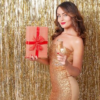 Молодая красивая женщина в золотом платье пьет шампанское, держа в руках красную подарочную коробку, веселится на вечеринке на блестящем золотом фоне