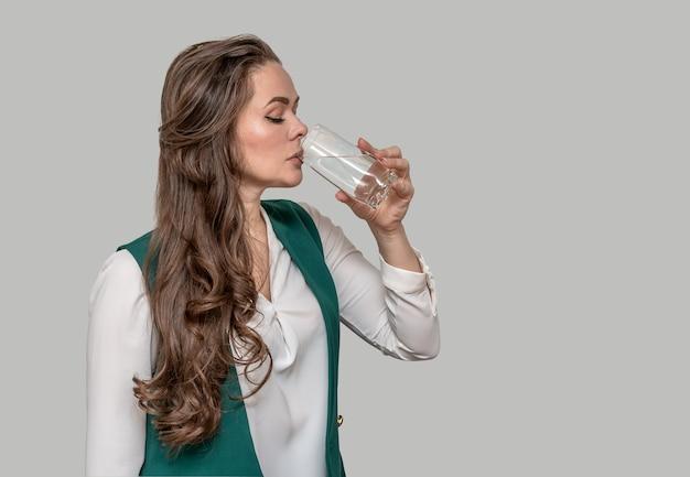 Молодая красивая женщина в зеленой куртке брюнетка с длинными волосами пьет воду из стакана