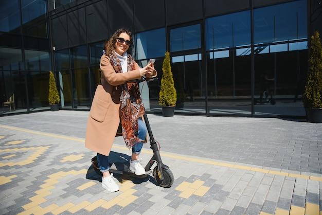 ジャケットを着た若い美女が笑顔で電動スクーターに乗って仕事をする