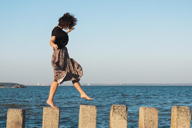 ビーチの岩の上を歩いて軽いカジュアルドレスの若い美しい女性
