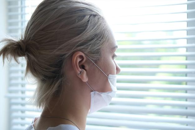 医療マスクの若い美しい女性が窓のそばに立っています。