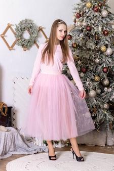 Молодая красивая женщина в розовом платье стоит возле новогодней елки