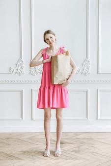 스튜디오의 흰색 배경에 제품 패키지가 있는 분홍색 드레스를 입은 젊은 미녀