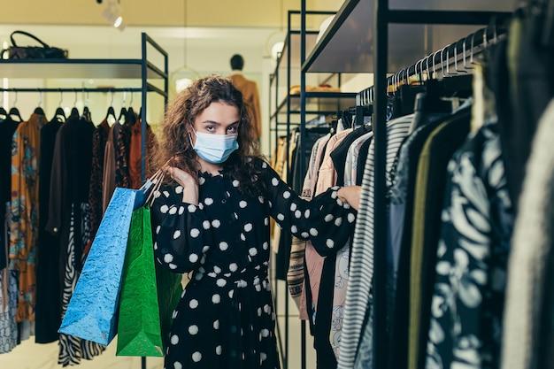 Молодая красивая женщина в защитной маске на лице выбирает одежду в магазине