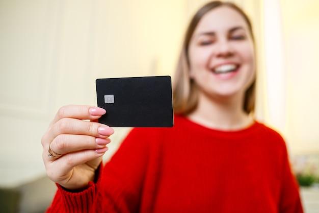銀行カードを保持している赤いセーターの若い美しい女性。オンライン購入用のクレジットカード。セレクティブフォーカス