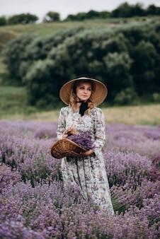 Молодая красивая женщина в романтическом платье в сиреневом поле.