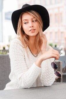 선글라스와 우아한 검은 모자에 세련 된 흰색 니트 스웨터에 젊은 아름 다운 여자는 야외 카페의 테이블에 앉아있다. 예쁜 소녀는 꿈을 꾸고 주말을 즐깁니다.