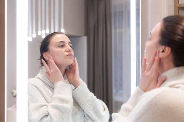 美容院のセーターを着た若い美女が鏡を見て、顔に触れ、次の手順を考え、自分自身を考える