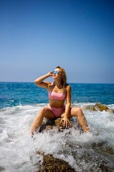 Молодая красивая женщина в купальнике сидит на каменистом пляже средиземного моря в турции. концепция отдыха на море. выборочный фокус