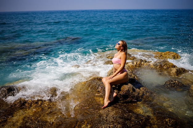 수영복에 젊은 아름 다운 여자는 터키에서 지중해의 바위 해변에 앉아있다. 바다 휴양의 개념. 선택적 초점