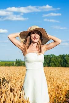 Молодая красивая женщина в белом платье и шляпа на поле мамаша.