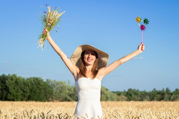 Молодая красивая женщина в белом платье и шляпе держит букет с полевыми цветами и игрушечным забралом на поле для мамочек.