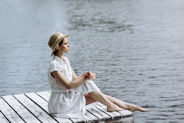 맨발로 흰 드레스에 젊은 아름 다운 여자는 태양 모자에 나무 부두에 앉아