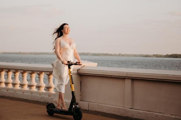 海の港で電動スクーターに乗って白いドレスを着た若い美しい女性、現代の女性、新世代、電気輸送、エコロジー、エコロジー輸送、夜明け、電動スケートボード