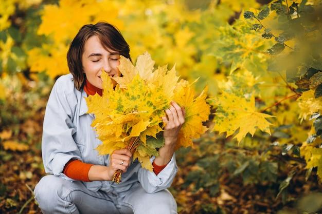 잎이 가득한가 공원에서 젊은 아름 다운 여자