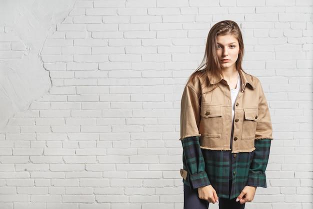 秋のジャケットの若い美しい女性は、白いレンガの壁の近くに立っています。コピースペースのあるポートレート。