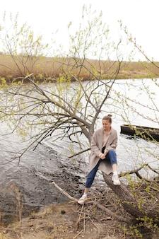 Молодая красивая женщина в бежевом пальто сидит на старом дереве у реки в ранний весенний день.