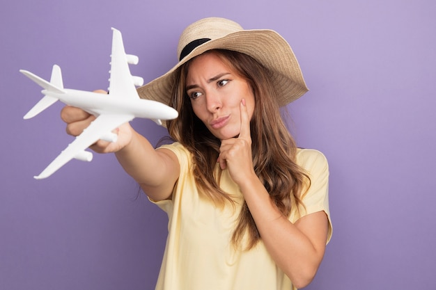 Молодая красивая женщина в бежевой футболке и летней шляпе держит игрушечный самолетик, глядя в сторону