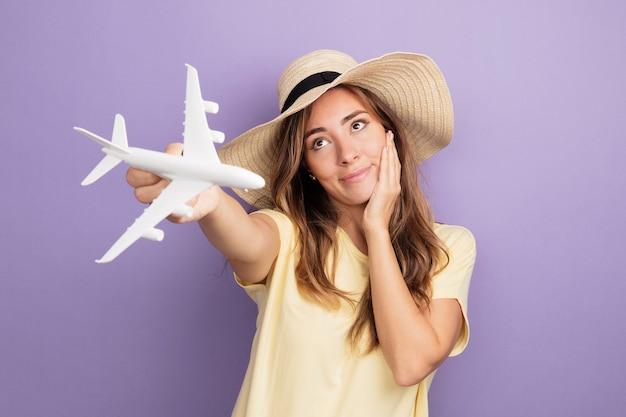 Молодая красивая женщина в бежевой футболке и летней шляпе держит игрушечный самолетик, глядя вверх