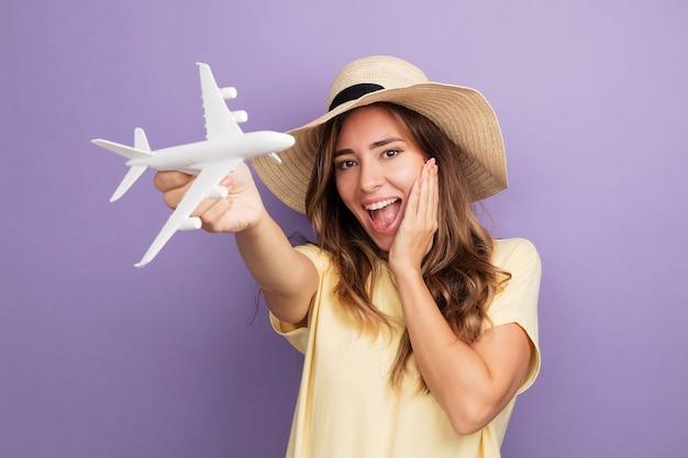 Молодая красивая женщина в бежевой футболке и летней шляпе держит игрушку, глядя в камеру, счастливый и взволнованный самолет, стоящий на фиолетовом фоне