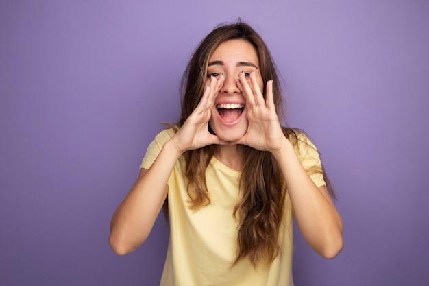 Молодая красивая женщина в бежевой футболке счастливая и возбужденная кричит руками возле рта
