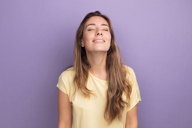 目を閉じて幸せで前向きな笑顔のベージュのtシャツの若い美しい女性