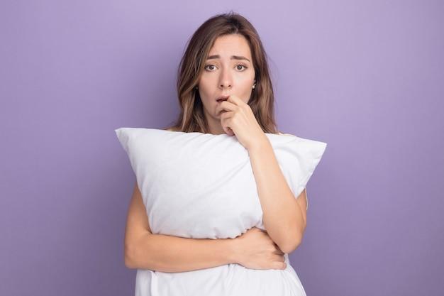Молодая красивая женщина в бежевой футболке держит белую подушку, глядя в камеру, подчеркнуто и обеспокоено, стоя на фиолетовом фоне