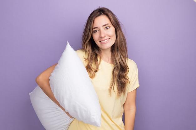 Молодая красивая женщина в бежевой футболке держит белую подушку, глядя в камеру с улыбкой на лице, стоящей над фиолетовым