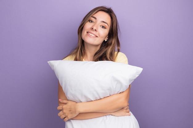 보라색 위에 서있는 얼굴에 미소로 카메라를보고 흰색 베개를 들고 베이지 색 티셔츠에 젊은 아름 다운 여자
