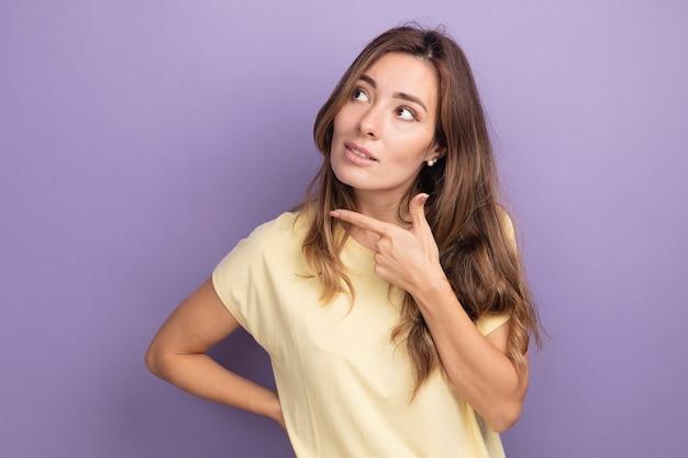 Молодая красивая женщина в бежевой футболке смотрит в сторону с улыбкой на умном лице, думая, стоя на фиолетовом фоне