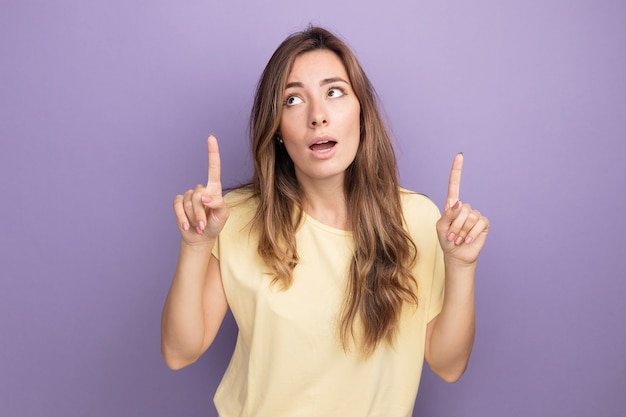 Молодая красивая женщина в бежевой футболке смотрит вверх с удивлением, указывая пальцами на указательные фигурки, стоящие над фиолетовым