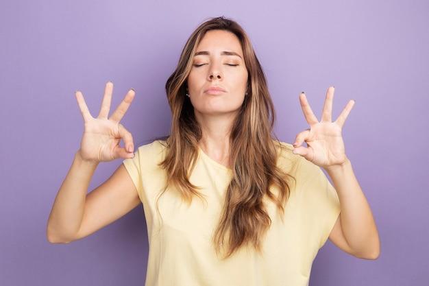 베이지색 티셔츠를 입은 젊고 아름다운 여성은 눈을 감고 휴식을 취하며 보라색 배경 위에 손가락이 서 있는 명상 제스처를 취합니다.