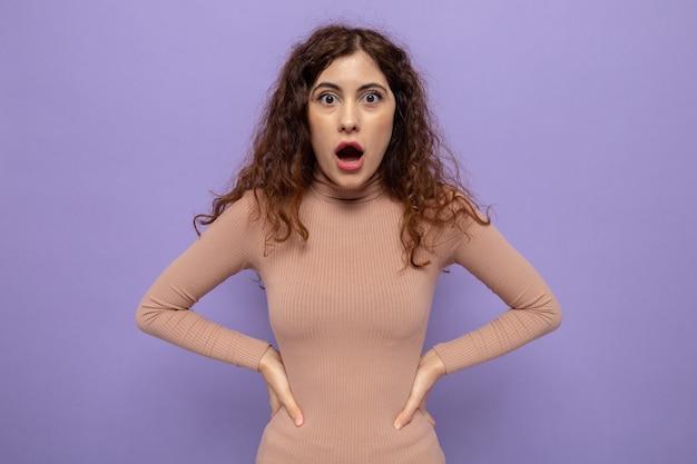 Молодая красивая женщина в бежевой водолазке изумила и удивила руками на бедрах, стоящими над фиолетовой стеной