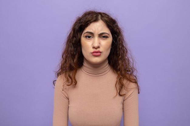 Молодая красивая женщина в бежевой водолазке недовольна, скривив рот с разочарованным выражением лица, стоя на фиолетовом