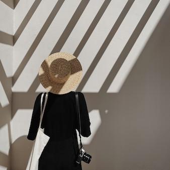 검은 드레스에 젊은 아름 다운 여자, 레트로 사진 카메라와 밀짚 모자 레일 햇빛 그림자와 흰 벽 근처에 머물