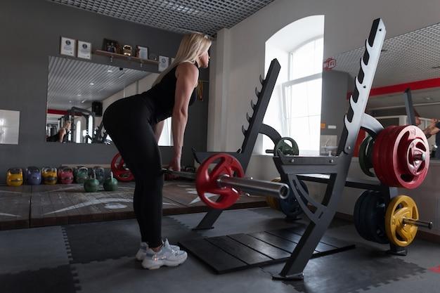 Молодая красивая женщина в черной спортивной одежде делает силовые упражнения со штангой в современном тренажерном зале