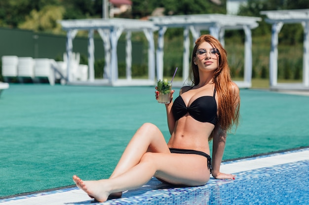 검은 수영복과 선글라스에 젊은 아름 다운 여자