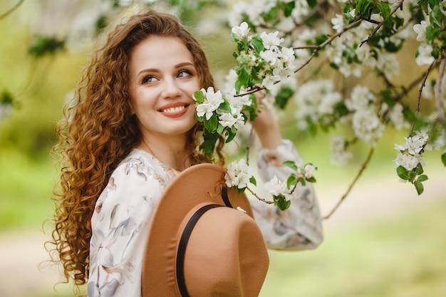 咲く庭の若い美しい女性。笑顔と春の木の花に触れて幸せである茶色の帽子をかぶっているかわいい女の子。季節と幸福の概念。
