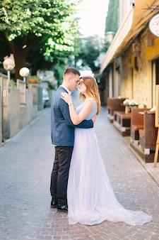 Молодая красивая женщина в голубом платье и красивый мужчина в куртке, прогуливаясь по улице с кафе в старом городе сирмионе. сирмионе, италия