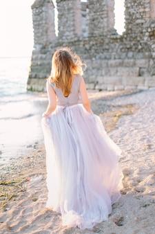 Молодая красивая женщина в голубом элегантном платье гуляя около озера garda и крепости в sirmione, италии. прекрасная прогулка в сирмионе