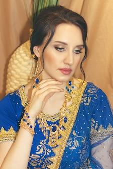 Молодая красивая женщина в голубом индийском платье сари