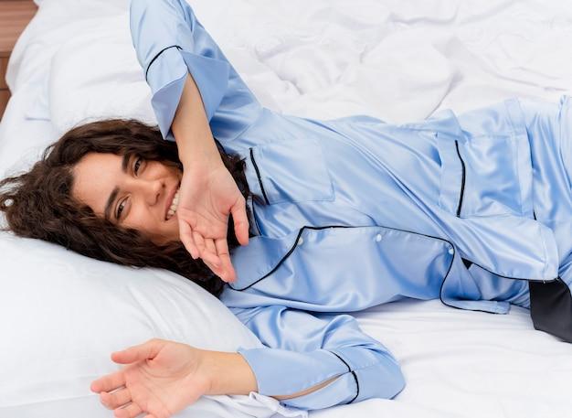 Молодая красивая женщина в синей пижаме, лежа на кровати, отдыхая на мягких подушках, счастлива и позитивна, наслаждаясь утренним временем в интерьере спальни на светлом фоне
