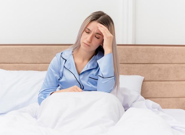 침실 인테리어에 두통을 가진 그녀의 머리를 만지고 침대에 앉아 파란색 잠옷에 젊은 아름 다운 여자