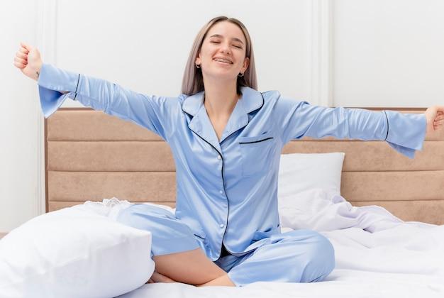 Молодая красивая женщина в синей пижаме сидит на кровати, счастливая и позитивная, просыпается, разводя руки гера в стороны в интерьере спальни на светлом фоне