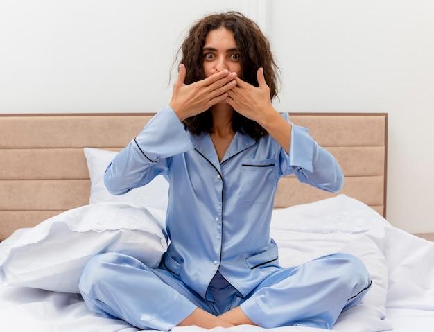 밝은 배경에 침실 인테리어에 손으로 입을 덮고 충격을 받고 카메라를보고 침대에 앉아 파란색 잠옷에 젊은 아름 다운 여자