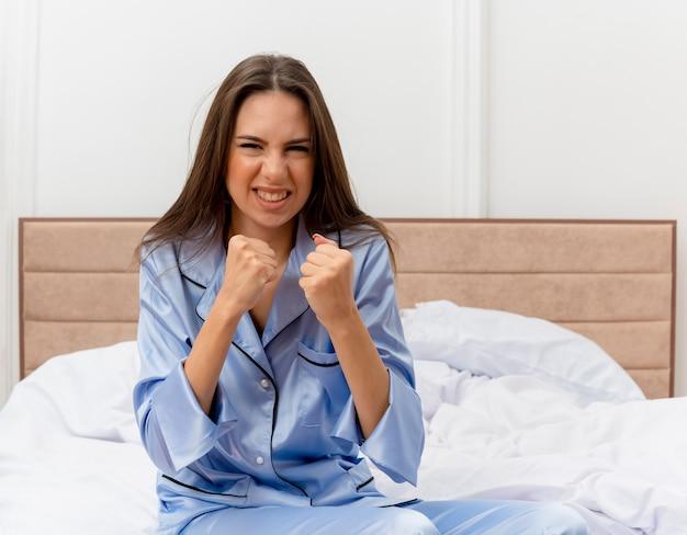 Молодая красивая женщина в синей пижаме сидит на кровати, глядя в камеру, сжимая кулаки с сердитым лицом в интерьере спальни на светлом фоне