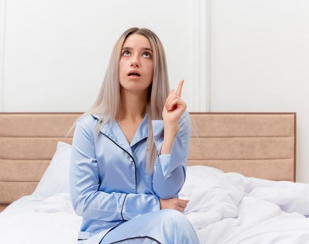 Молодая красивая женщина в синей пижаме сидит на кровати, глядя вверх, показывая указательный палец в интерьере спальни на светлом фоне