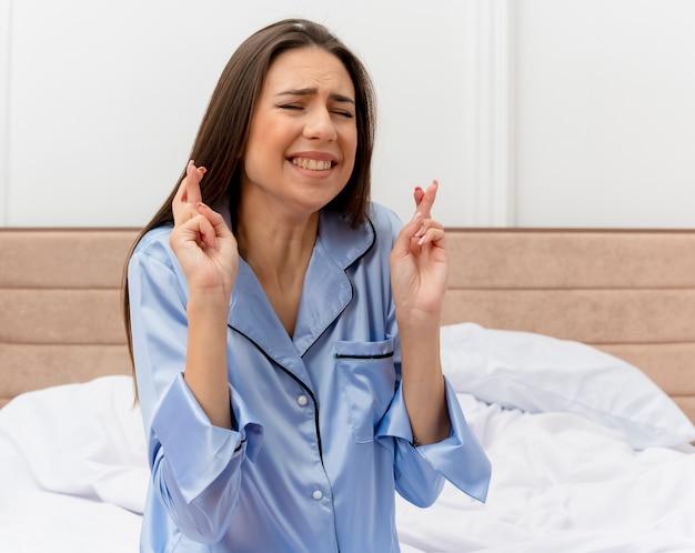 Молодая красивая женщина в синей пижаме сидит на кровати и загадывает желаемое, скрещивая пальцы с выражением надежды в интерьере спальни на светлом фоне