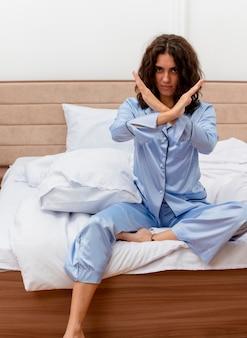 Молодая красивая женщина в синей пижаме сидит на кровати, делая знак остановки, скрещивая руки, глядя с серьезным лицом в интерьере спальни на светлом фоне