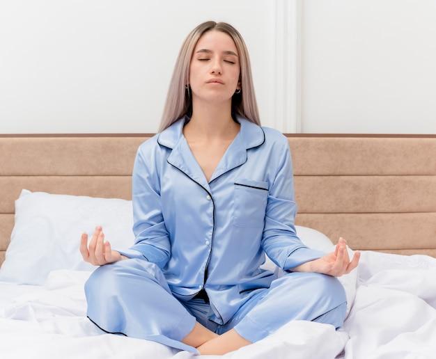 침실 인테리어에 손가락으로 명상 제스처를 만드는 닫힌 눈으로 편안한 침대에 앉아 파란색 잠옷에 젊은 아름 다운 여자